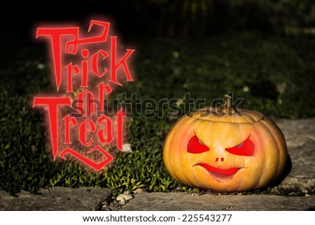 Halloween trick or treat scary pumpkin jack-o-lantern with a smile on dark green grass  - stock photo