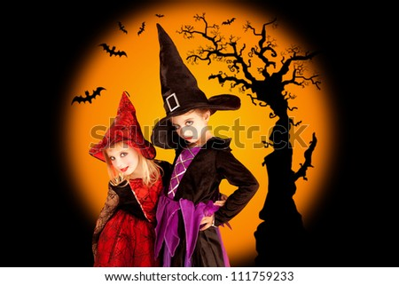 Halloween two children girls with tree and bats on orange background - stock photo