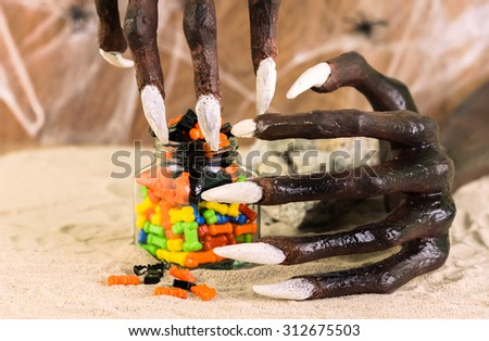 Halloween witch hand and colorful candies close up - stock photo