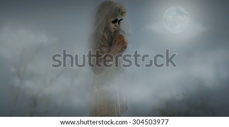 Halloween witch holding pumpkin outdoors at night - stock photo