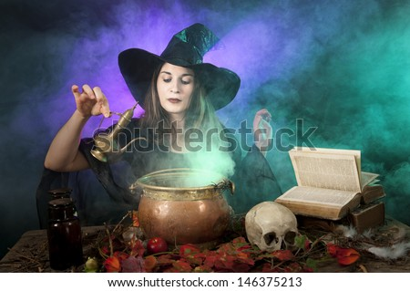 halloween witch making a potion - stock photo