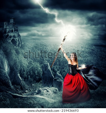 halloween witch making magic and controls the weather. shoots lightning into the sky from the magical staves - stock photo