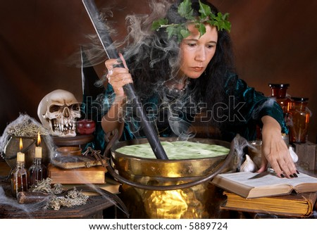 Halloween witch stirring in green poison soup in her cauldron - stock photo