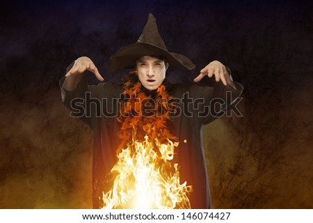 halloween witch with fire - stock photo