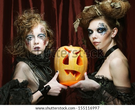 Halloween witches  with carved pumpkin  - stock photo