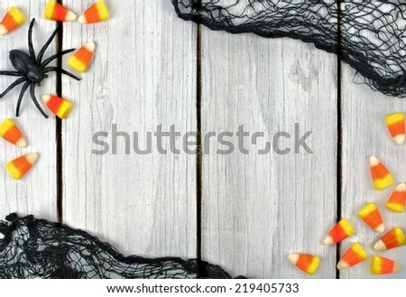 Halloween wooden background with candy corn and black cloth frame - stock photo