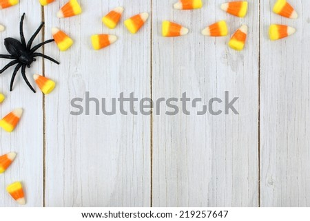 Halloween wooden background with candy corn and spider border - stock photo