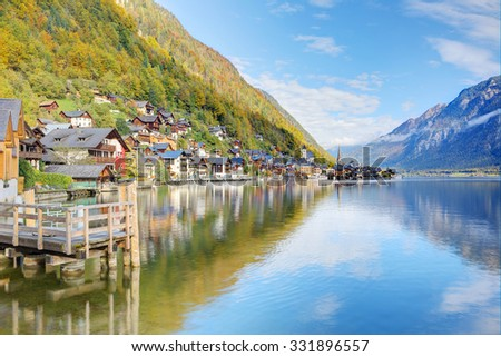 Hallstatt under blue sunny sky with beautiful reflections on smooth lake water ~ An amazing lakeside village in Salzkammergut region of Austria, in the brisk colorful autumn season - stock photo