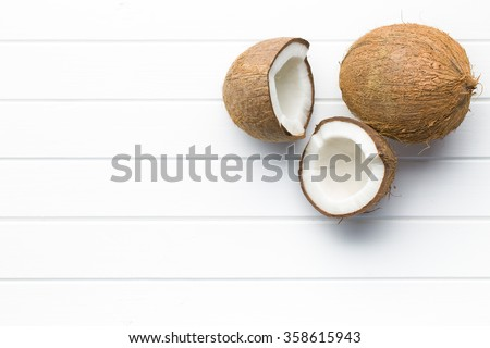 halved and whole coconut on white table - stock photo