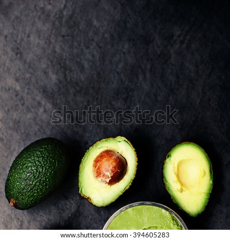 Halved and  whole ripe avocados over black background. Top view. - stock photo