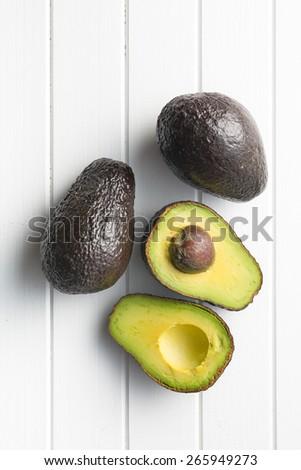 halved avocado on white table  - stock photo