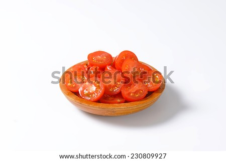 halved cherry tomatoes served in the wooden bowl - stock photo