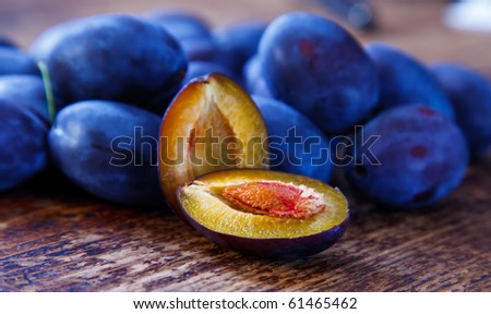 Halved plum and other whole plums on the table - stock photo