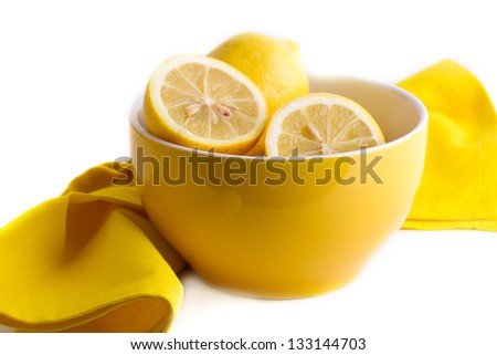 Halves and whole lemons in a bowl next to a yellow napkin - stock photo