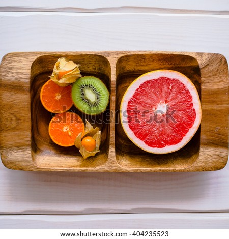 Halves of fruits on the wooden square dish - stock photo