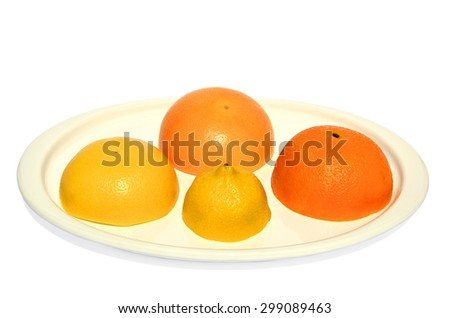 Halves of yellow and red grapefruits, orange and lemon set on white plate - stock photo