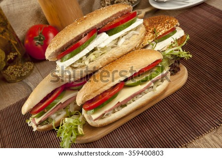 Ham and cheese salad submarine sandwiches from fresh baguette. - stock photo