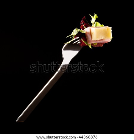 Ham and cheese sallad on a fork isolated on black - stock photo