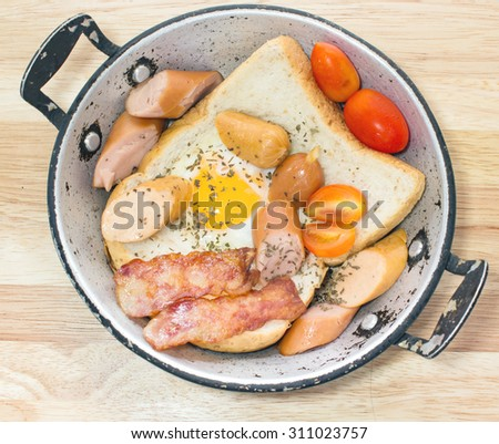 Ham and Egg. Bacon and Egg. Salted egg and sprinkled with black pepper. English breakfast. Grilled bacon, and bread in pan ready to serve - stock photo