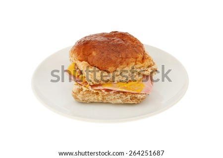 Ham and mustard wholemeal bread roll on a plate isolated against white - stock photo