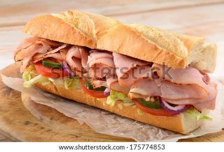 Ham and salad submarine sandwich from freshly cut baguette on rustic wooden bread board. - stock photo