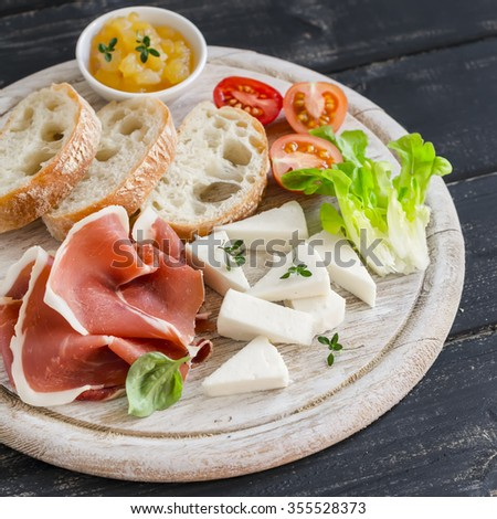 ham, cheese, tomatoes and ciabatta bread served on a light wooden board on a dark wooden surface. Tasty Breakfast, snack or delicious appetizer to wine - stock photo