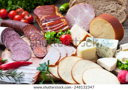 Ham, salami, sausages and cheese with bread and tomato - stock photo
