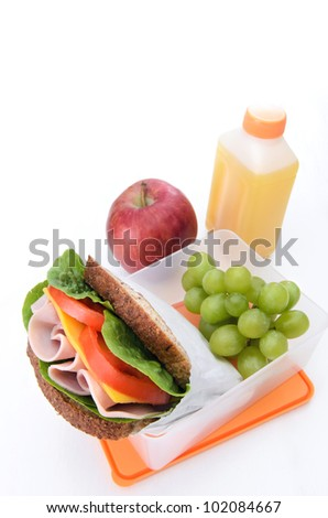 Ham sandwich, apple, green grapes and orange juice in a lunch box isolated on white - stock photo