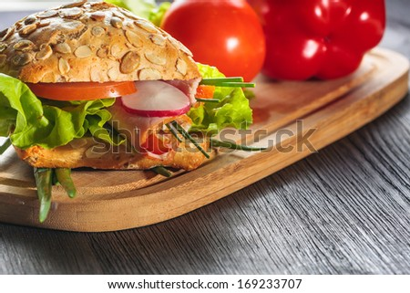 ham sandwich with lettuce on wood background - stock photo