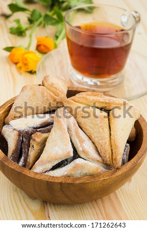 Hamantaschen cookies for Purim with cup of tea on a wooden table - stock photo
