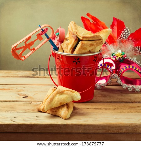 Hamantaschen cookies in bucket with grogger noise maker and carnival mask - stock photo