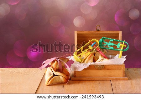 Hamantaschen cookies or hamans ears and mask for Purim celebration (jewish holiday) and glitter background  - stock photo