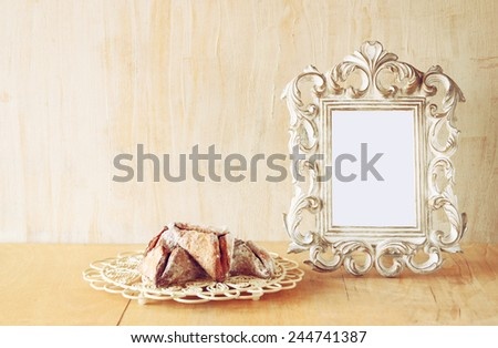 Hamantaschen cookies or hamans ears and vintage frame for Purim celebration (jewish holiday)  - stock photo