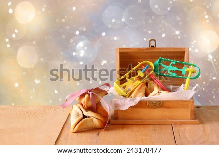 Hamantaschen cookies or hamans ears celebration (jewish holiday) and glitter background  - stock photo