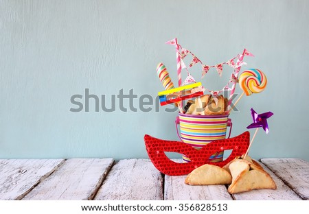 Hamantaschen cookies or hamans ears,noisemaker and mask for Purim celebration (jewish carnival holiday) . selective focus - stock photo