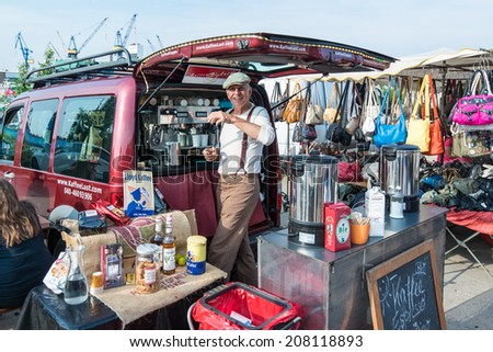 Hamburg, Germany - July 20, 2014: A Hamburg guy is selling fresh coffee on the traditional Hamburg Fish Market in the early Sunday Morning on July 20, 2014 in Hamburg, Germany. The Fish Market is - stock photo