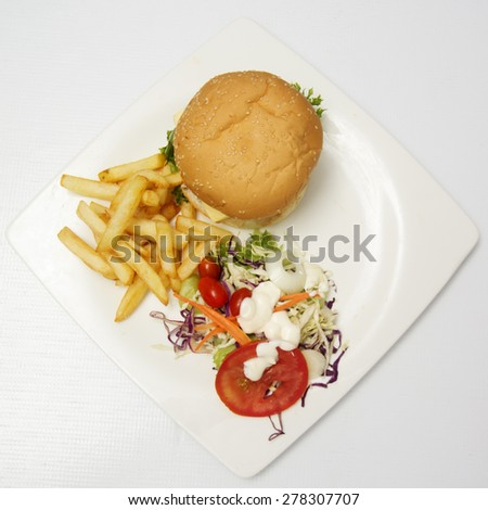 Hamburger beef ,french fries and vegetable salad on the Plate (Top view) - stock photo