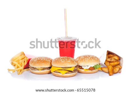 hamburger, cheeseburger, fishburger, soda drink, french fries and roast potatoes (focus on central burger) - stock photo