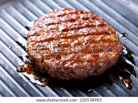 Hamburger cooking on the grill  - stock photo