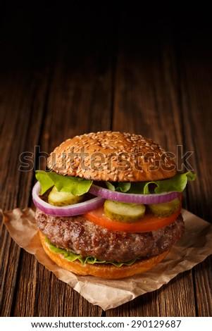 Hamburger. Hamburger on wooden background. Vintage Hamburger. Home made burger. Fastfood meal. Pub burger. Delicious Hamburger. Gourmet hamburger. Hamburger on wooden table. Rustic Hamburger, bun. - stock photo