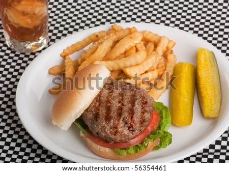 Hamburger on a bun with tomato and lettuce with french fries, pickles and a drink - stock photo