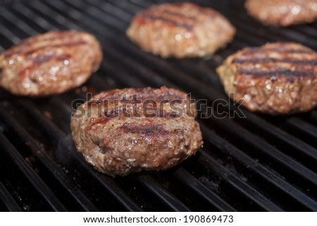 Hamburger patties cooking on a grill. - stock photo