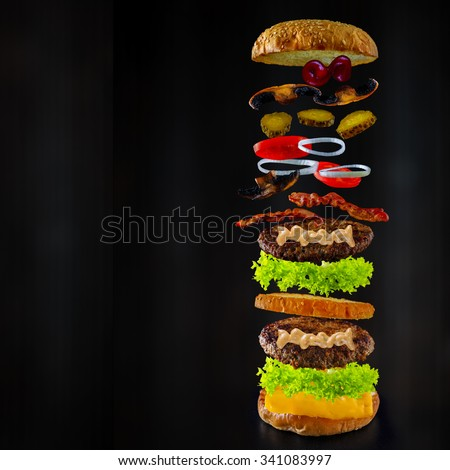 Hamburger stacked high with a juicy beef patty, cheese, fresh lettuce, onion and tomato with flying ingredients and copyspace - stock photo