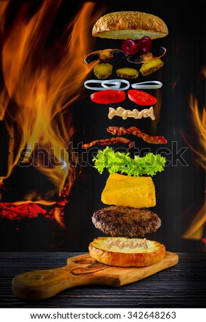 Hamburger stacked high with a juicy beef patty with flying ingredients - flames in the background - stock photo