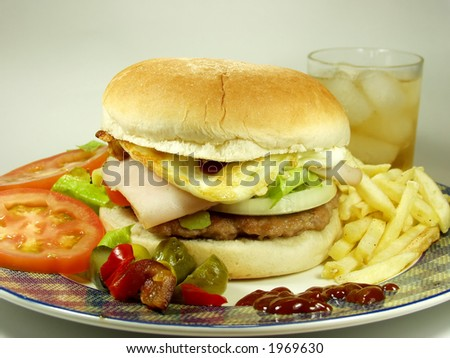 hamburger whit egg and french fried, salad and ice tea for drink - stock photo