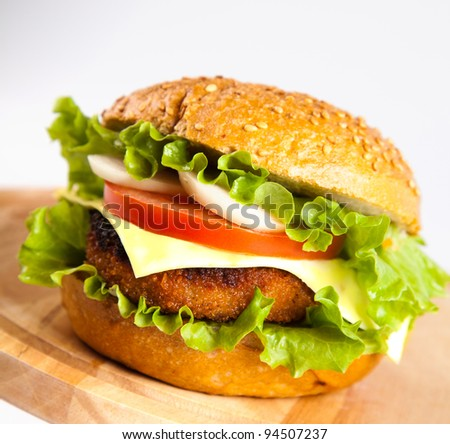 hamburger with fish cutlet and vegetables on wooden board - stock photo