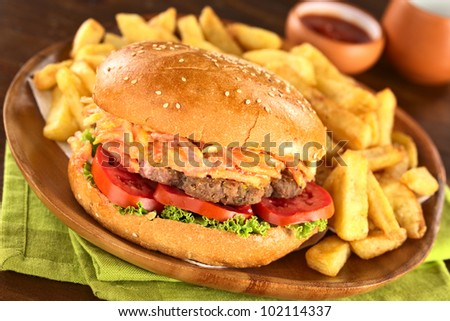 Hamburger with French fries on rustic wooden plate with ketchup (Selective Focus, Focus on the front of the hamburger) - stock photo
