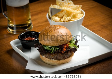 Hamburger with fries and beer. - stock photo