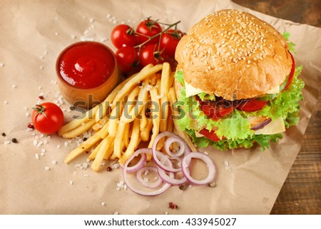 Hamburger with fries on paper background - stock photo