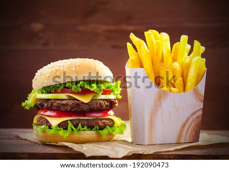 Hamburger with fries on wood board - stock photo